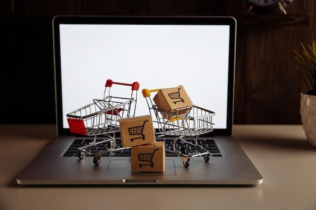 Pudełka papierowe w wózkach supermarketów na klawiaturze laptopa. koncepcja zakupów online.