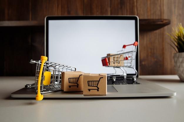 Pudełka papierowe w wózkach supermarketów na klawiaturze laptopa