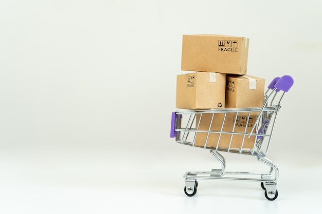 Pudełka papierowe w wózku z kartą kredytową. koncepcja zakupów online lub e-commerce