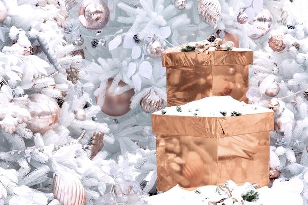 Pudełka prezentów w złotym kolorze pokryte śniegiem stoją w pobliżu choinki ozdobionej różnymi kulkami o pastelowych kolorach. koncepcja nowego roku, wystrój, ferie zimowe.