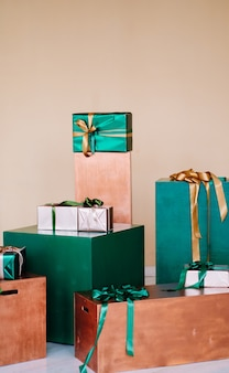 Pudełka prezentowe o różnych rozmiarach w kolorze zielonym i brązowym. teren na świąteczną sesję zdjęciową. świętujemy i gratulujemy nowego roku, urodzin, walentynek.
