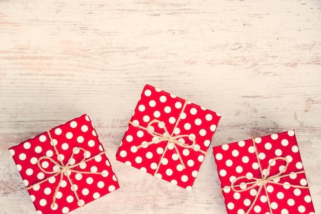 Pudełka prezentowe w czerwone kropki rozrzucone na białym drewnie, efekt vintage.