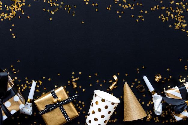 Pudełka prezentowe w różnych papierach do pakowania ze złotym wzorem i akcesoriach imprezowych nad złotymi cekinami w kształcie gwiazdy na czarnym tle.