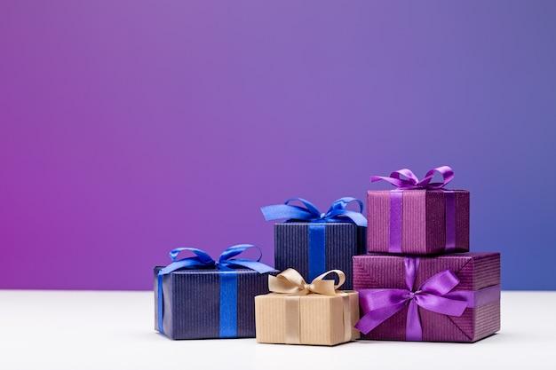 Pudełka prezentowe z eleganckiego, wielobarwnego papieru ze wstążkami i kokardkami na niebieskim tle.