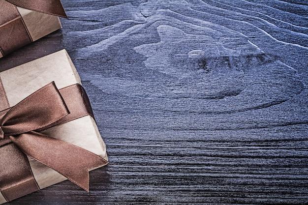 Pudełka prezentowe z obecnymi taśmami na desce drewnianej