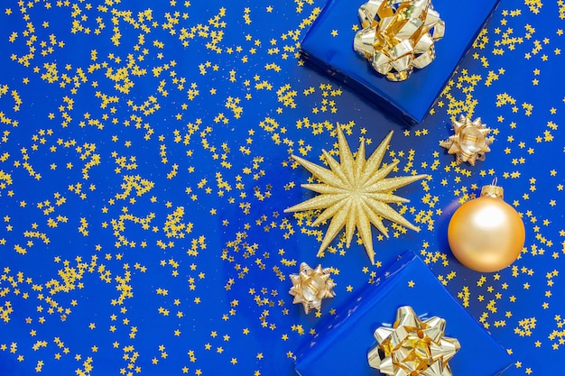 Pudełka prezentowe ze złotą kokardką i bombkami na niebieskim tle, złote błyszczące gwiazdki z brokatem na niebieskim tle, koncepcja bożego narodzenia, flat lay, widok z góry