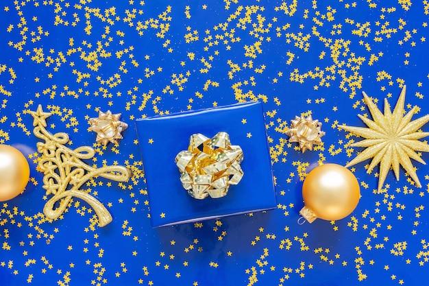 Pudełka prezentowe ze złotym łukiem i jodłą z bombkami na niebieskim tle, złote błyszczące gwiazdy brokatu na niebieskim tle