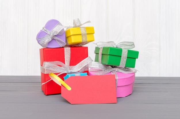 Pudełka upominkowe związane są wstążką ze słowami dzień boxowania i czerwoną metką na białej powierzchni drewna