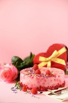 Pudełka w kształcie serca, róże, ciasto malinowe ze świeżymi jagodami, rozmarynem i suchymi kwiatami. koncepcja walentynki. przedstaw z miłością