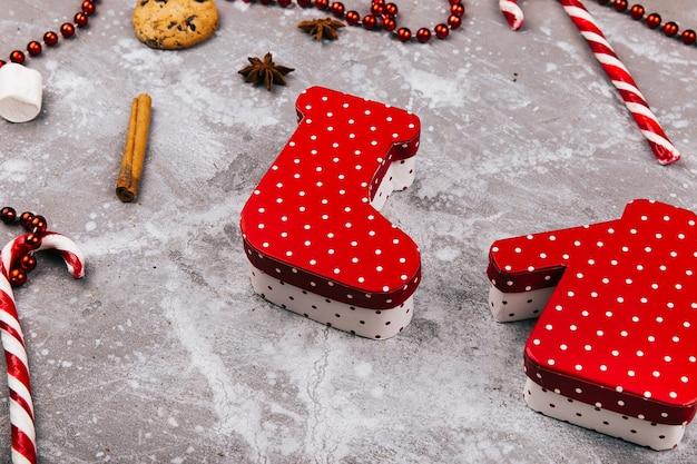 Pudełka w kształcie świątecznych skarpet i swetra leżą na szarej podłodze otoczone ciastkami, przyprawami i czerwonymi białymi cukierkami