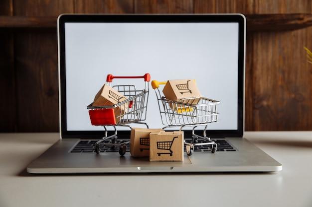 Pudełka w wózkach na klawiaturze laptopa. koncepcja zakupów online.