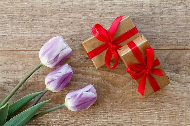 Pudełka z czerwonymi wstążkami i pięknymi tulipanami na drewnianych deskach. widok z góry. koncepcja dawania prezentu na święta.