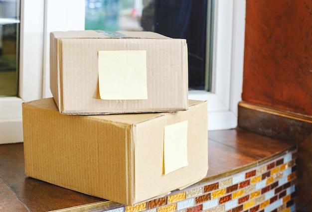 Pudełka z dostawą na wyciągnięcie ręki w pobliżu drzwi do domu. bezkontaktowa dostawa żywności.