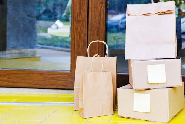 Pudełka z dostawą, torby papierowe na wyciągnięcie ręki w pobliżu drzwi do domu. dostawa zbliżeniowa. bezpieczne zakupy e-commerce kupuj paczki do domu.