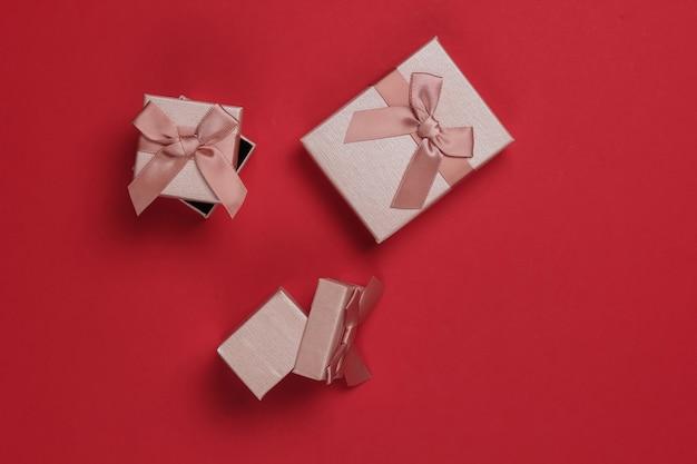 Pudełka z kokardkami na czerwonym tle studio. kompozycja na boże narodzenie, urodziny lub wesele.