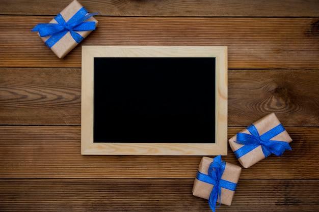 Pudełka z niebieską wstążką i pusta tablica na drewnianym stole. widok z góry.