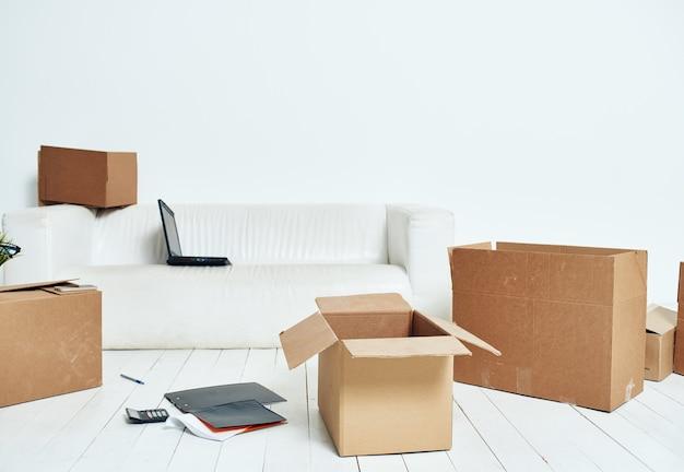 Pudełka z rzeczy białą kanapą rozpakowywanie biura w ruchu