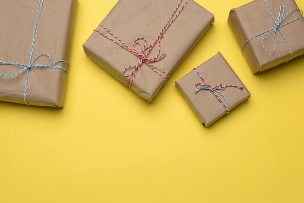 Pudełka zawinięte w brązowy papier i przewiązane sznurem na żółtej powierzchni