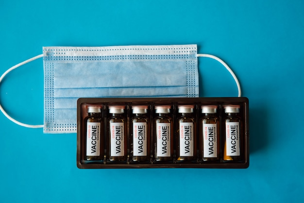 Pudełko ampułek z etykietą i maską medyczną na niebieskim tle z miejsca na kopię, zbliżenie.