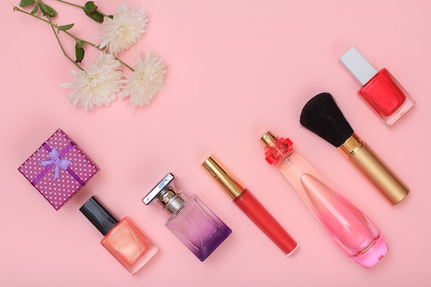 Pudełko, butelki z lakierem do paznokci, perfumami, pędzlem, szminką i kwiatami na różowym tle. kosmetyki i akcesoria dla kobiet. widok z góry.