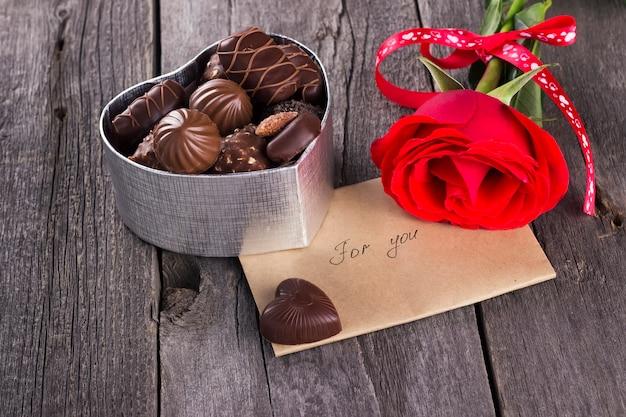 Pudełko czekoladek, czerwona róża na ciemnym tle