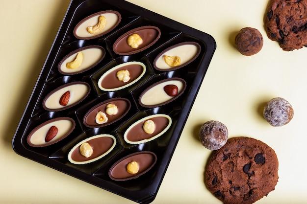 Pudełko czekoladek z orzechami i ciasteczkami z kawałkami czekolady na żółtym tle widok z góry
