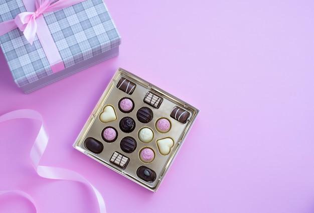 Pudełko czekoladowych pralinek z różową kokardką na różowym tle