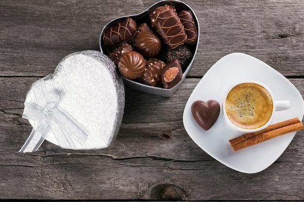 Pudełko czekolady, filiżanka kawy na drewnianym tle. widok z góry