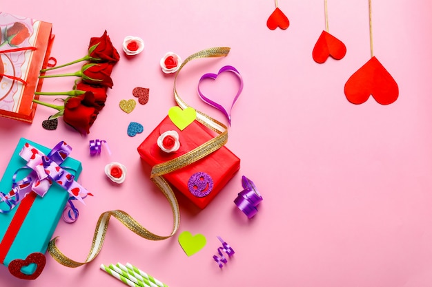 Pudełko, czerwona róża i mały kształt serca na różowym tle. koncepcja walentynki