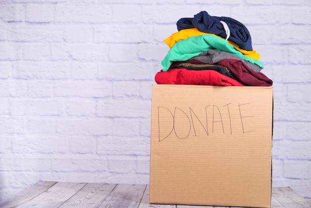 Pudełko darowizny z ubraniami darowizny na drewnianym tle