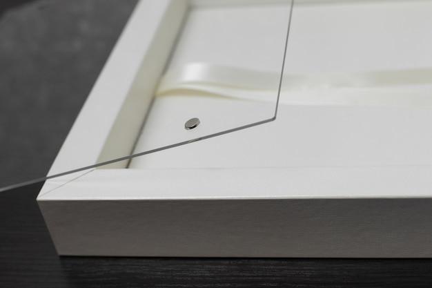 Pudełko dla ślubnego albumu fotograficznego na drewnianym tle. stylowe pudełko na rodzinną fotoksiążkę z copyspace. pudełko na prezent ze wstążką ze szklaną pokrywką.
