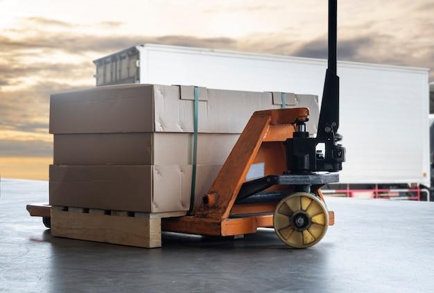 Pudełko do pakowania na regale paletowym z ręcznym wózkiem paletowym wózek towarowy zaparkowany ładowanie w magazynie dokowym