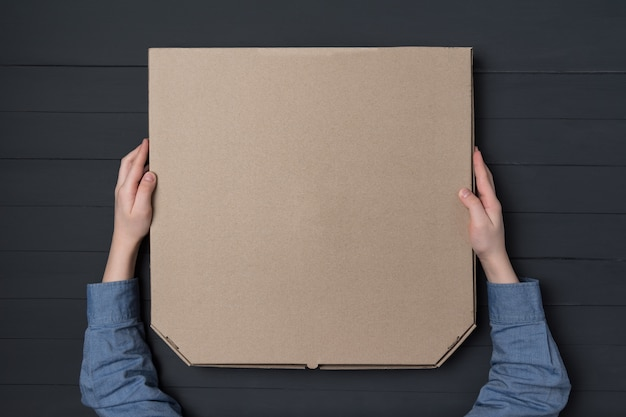 Pudełko do pizzy w rękach dzieci. czarna ściana. widok z góry. skopiuj miejsce