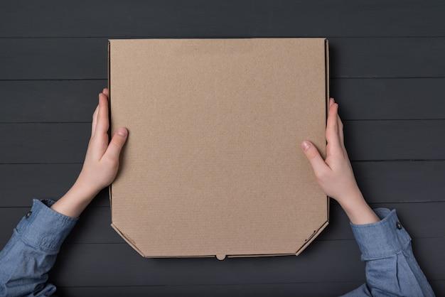 Pudełko do pizzy w rękach dzieci. czarne tło. widok z góry. skopiuj miejsce