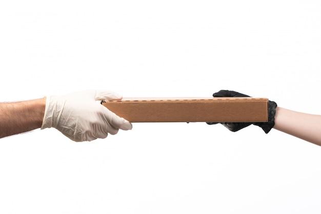 Pudełko dostawy, widok z przodu, przenoszone od kobiety do mężczyzny w rękawiczkach na białym tle