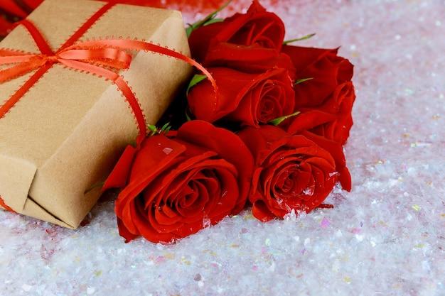 Pudełko i bukiet pięknych czerwonych róż na błyszczącym śniegu. koncepcja walentynki.