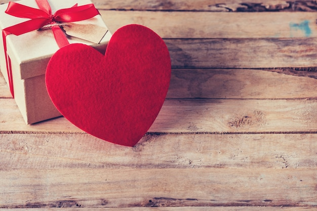 Pudełko i czerwone serce na drewnianym stole z kosmosu