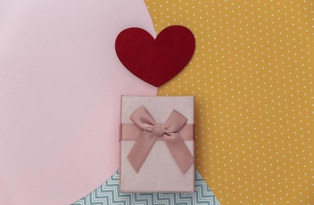 Pudełko i czerwone serce na tle kreatywnych kolorowy papier. minimalizm