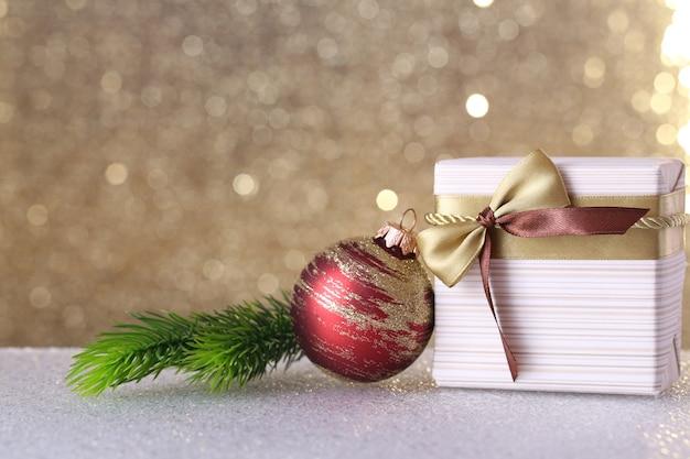 Pudełko i dekoracje świąteczne na stole na błyszczącej powierzchni