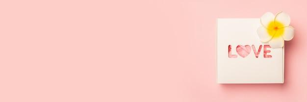 Pudełko i kwiaty na pastelowo różowej powierzchni