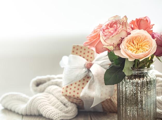 Pudełko i świeże róże w szklanym wazonie na walentynki lub dzień kobiet. koncepcja wakacje.