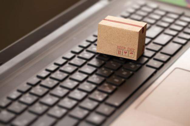 Pudełko kartonowe na klawiaturze notebooka. zakupy online, handel elektroniczny i koncepcja usług dostawy.