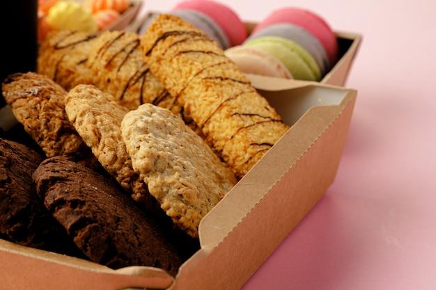 Pudełko kartonowe z ciasteczkami owsianymi na różowym stole