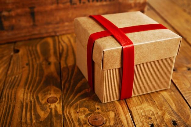 Pudełko kartonowe z papieru rzemieślniczego zamknięte i owinięte czerwoną jedwabną taśmą na rustykalnym drewnianym stole, blisko ostrości