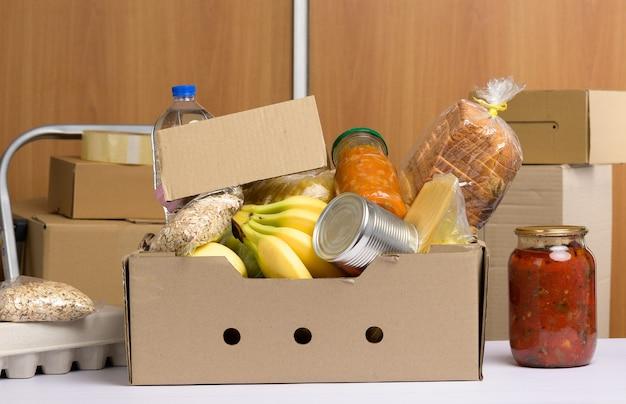 Pudełko kartonowe z różnymi produktami, owocami, makaronem, olejem słonecznikowym w plastikowej butelce i konserwą. koncepcja darowizny