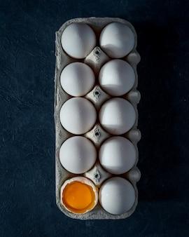 Pudełko kartonowe z surowymi jajkami, jedno rozbite, na granatowym stole. widok z góry