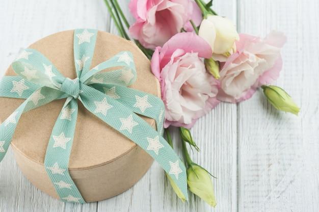 Pudełko kwiatowe i upominkowe eustoma z zieloną wstążką