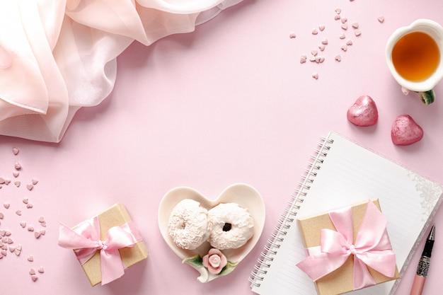 Pudełko lub pudełko na prezent i kwiaty na różowym blacie stołu. leżał płasko.