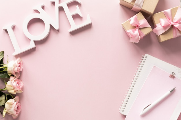 Pudełko lub pudełko na prezent i kwiaty na różowym blacie stołu.
