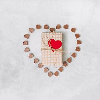 Pudełko między słodkimi czekoladowymi cukierkami w formie serca